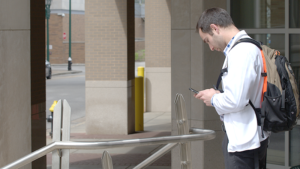 Man in a white lab coat with backpack looks down at phone.