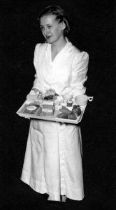 A Barnes Hospital employee with an assembled patient's tray, c. 1950s.