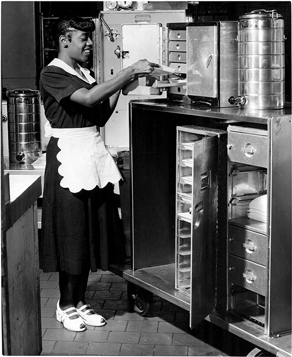 A Barnes Hospital pantry maid with one of the specially designed carts used in the airline model of food service, c. 1950s.