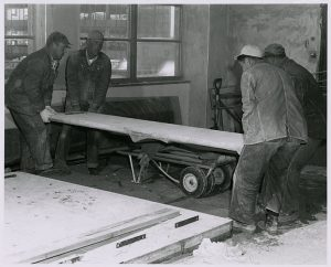 Workers moving the set concrete panels, circa 1960