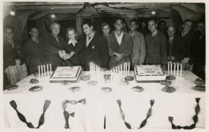 """A group of smiling men and a woman stand behind a table decorated with 2 cakes, many candles, and streamers that spell out VF VJ. 3 of the group hold a knife cutting into one of the cakes which reads """"Victory."""""""