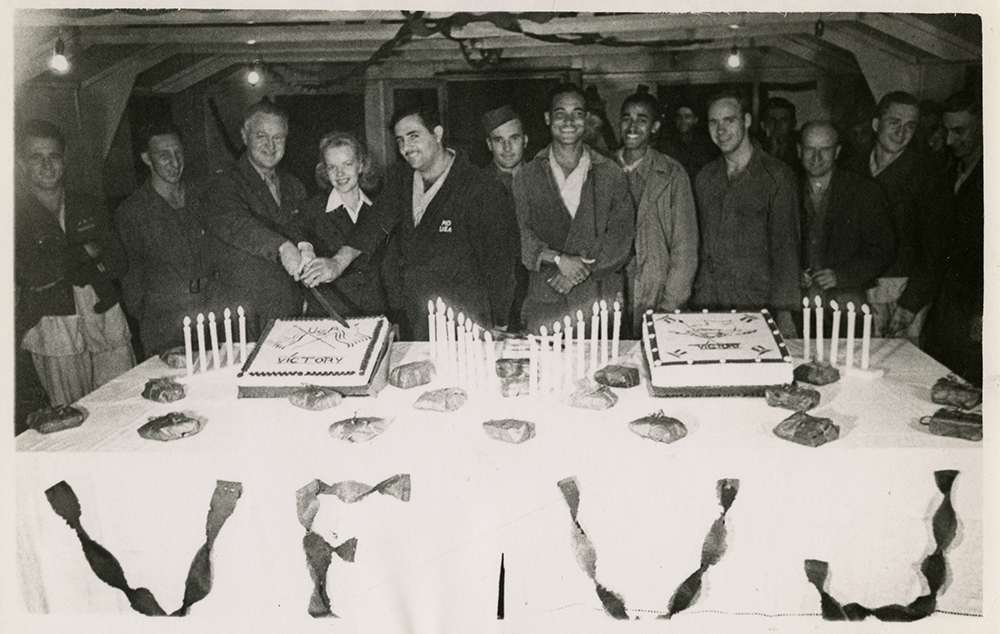 Col. Lee Cady, Miss Lillian Hansen, and patients cutting a cake at the party celebrating the end of World War II, 21st General Hospital, then stationed in Mirecourt, France, 1945