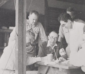 5 American and Japanese men in uniform review a document on a table.
