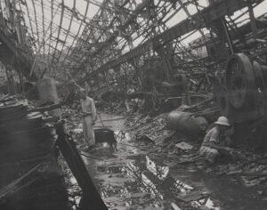 A photo taken inside the skeletal frame of a destroyed building filled with debris.