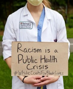 """Medical professional holds a sign saying """"Racism is a public health crisis. #WhiteCoatsForBlackLives"""""""